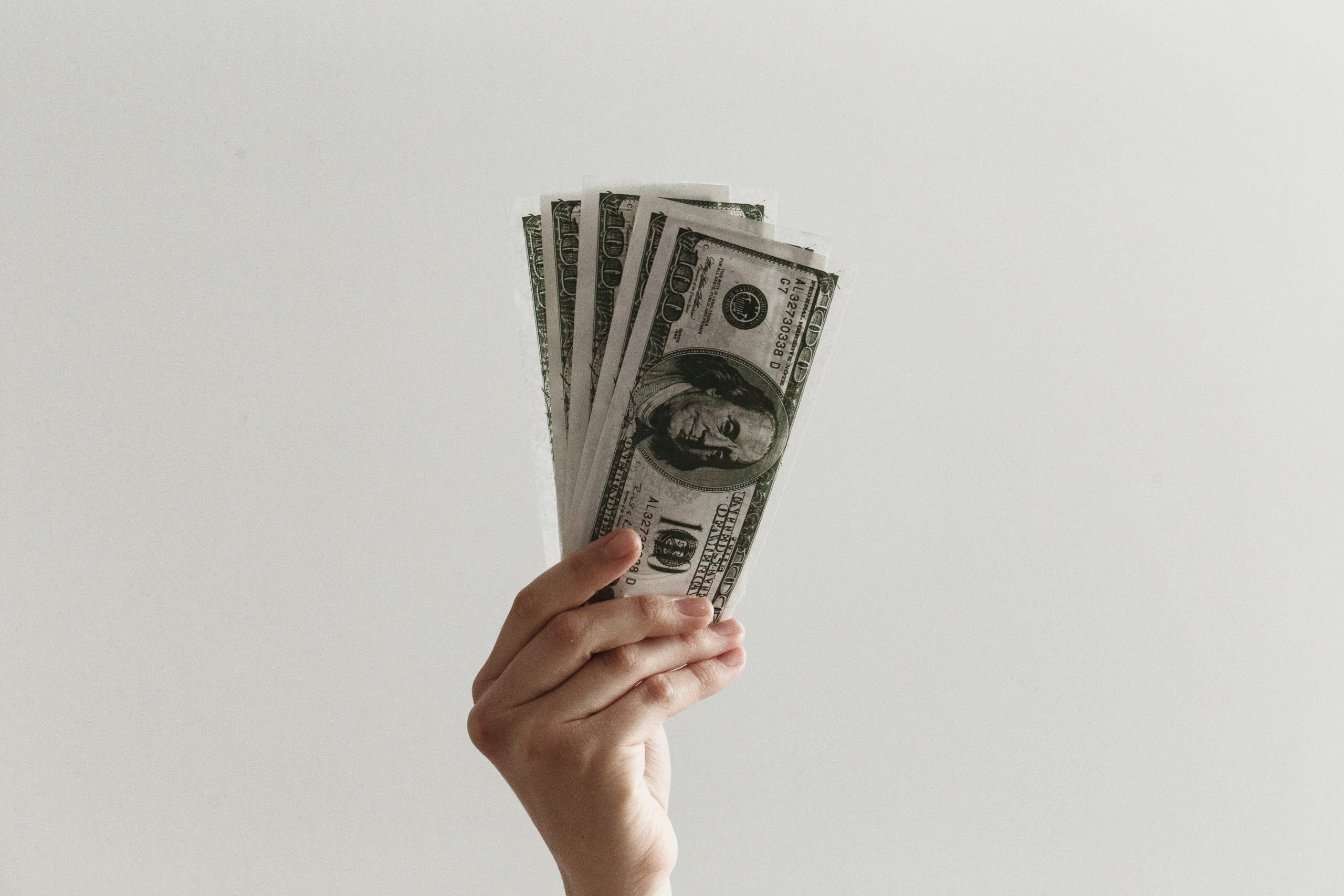 Picture of hand holding money for article How to Afford Living in NYC