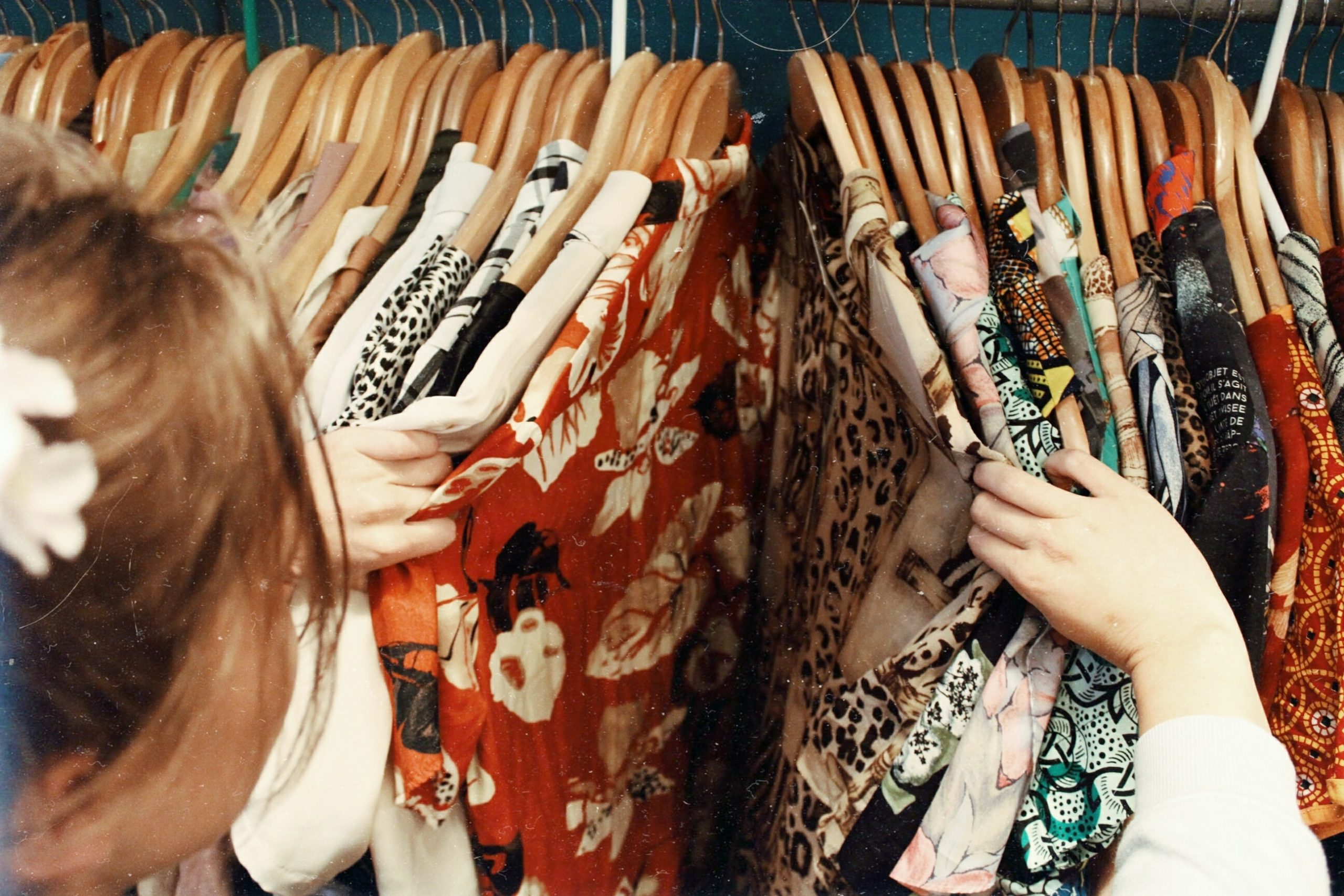 Girl searching through thrift store for article How To Thrift Like A Pro