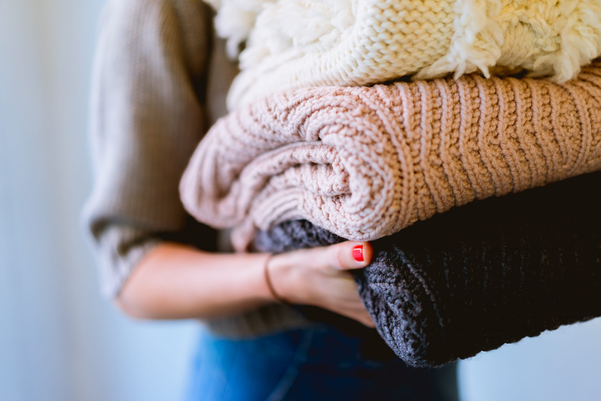 girl holding sweaters for article The Best Winter Sweaters Under $50