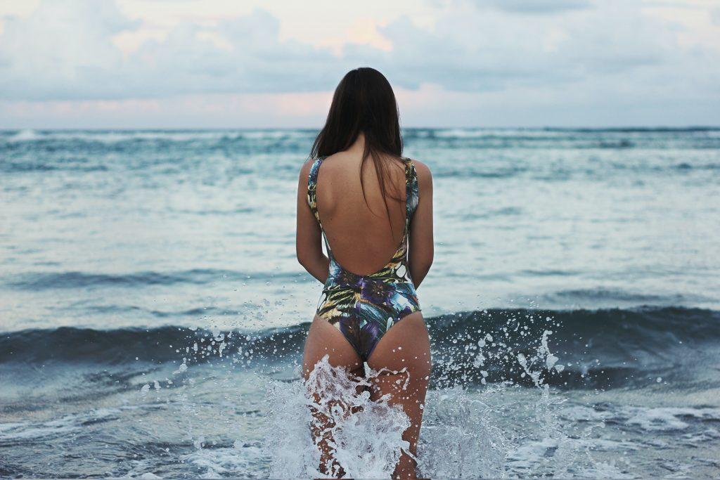 Girl in one piece standing in ocean for best sustainable swimwear brands